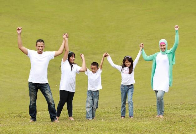 幸せな家族が一緒に手を上げる