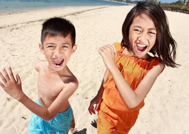 幸せな男の子と女の子がビーチで実行されているの肖像画