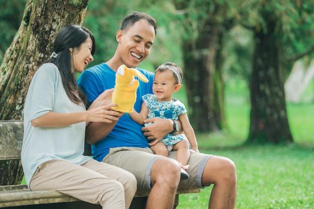 Счастливая семья сидит на скамейке в парке и играет с куклой