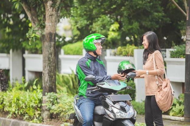 Коммерческий водитель мотоцикла, дающий шлем своему клиенту
