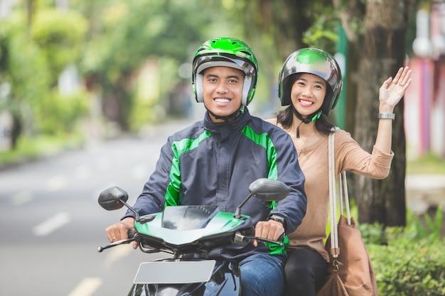 商用バイクに座って、さようならを振る乗客