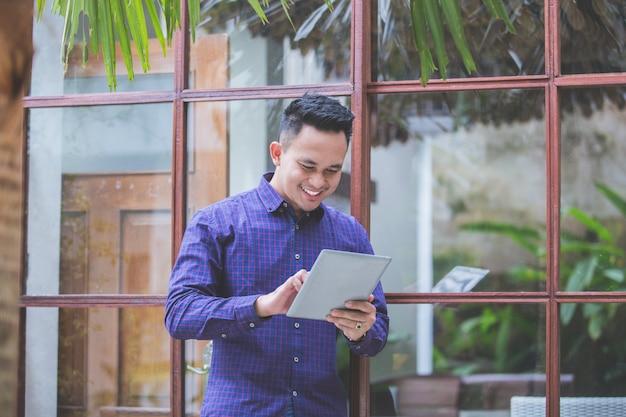 Красивый современный человек улыбается с планшета
