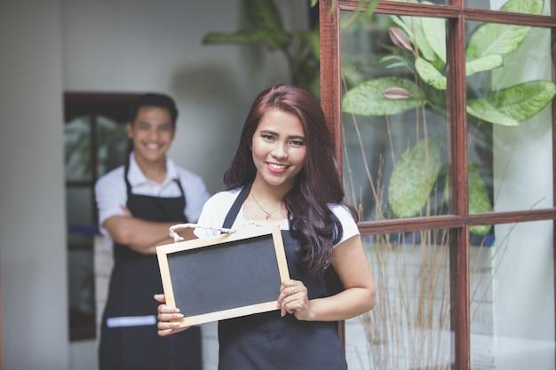 Официантка, стоящая перед кафе, приглашает людей войти