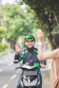 Женщина, стоящая на тротуаре, заказывает мотоцикл такси