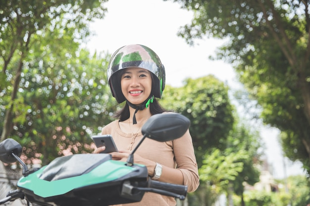 バイクに乗っている間携帯電話を使用している女性