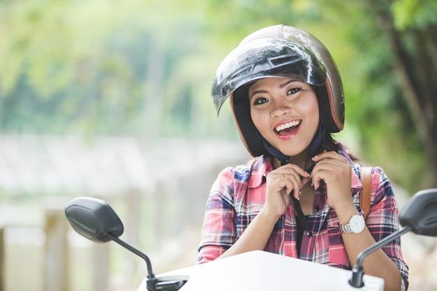 バイクに乗る前にヘルメットを身に着けている若いアジア女性