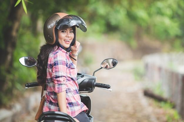 公園でバイクに乗る若いアジア女性