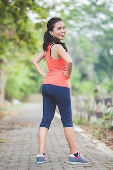 公園で屋外運動をしている若いアジア女性ストレッチ