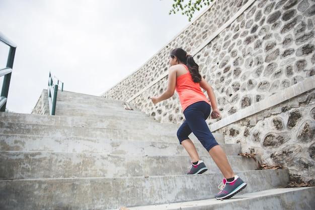 若いアジアの女性が公園で屋外の運動をして、ジョギング
