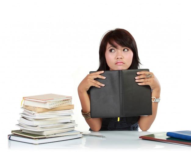 本を持つ若い大人アジア女性