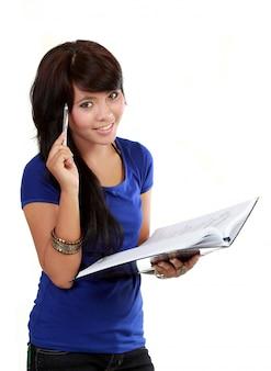 考えて、ペンとノートを保持しているかなり若い女性