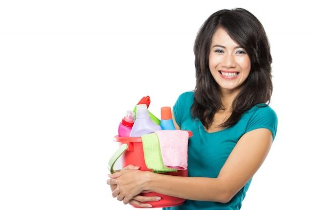 何かをする準備ができているクリーニング製品がいっぱい入ったかごを保持している女性
