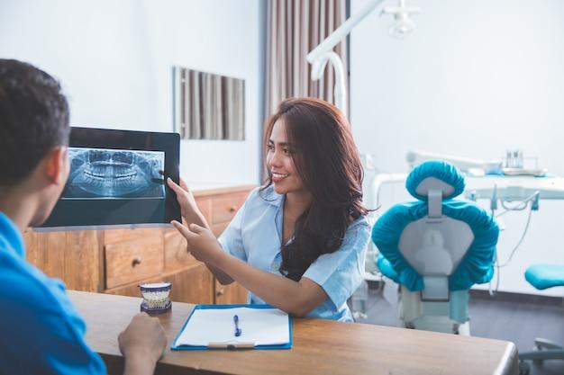 Стоматолог, разговаривая с ее пациентом, объясняя рентген