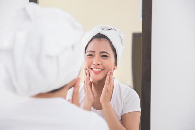 Женщина наносит на лицо лосьон для ухода за кожей