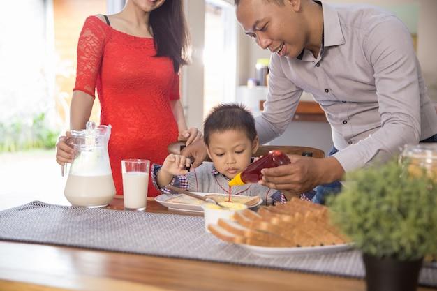 朝食を一緒に楽しんで幸せなアジア家族