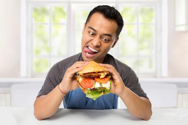 若い男はハンバーガーを食べたいという大きな欲望を持っています