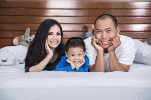 ベッドで幸せなアジア家族