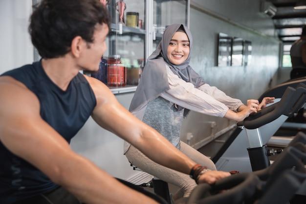 Мусульманка хиджаб и друг в тренажерном зале делают кардио упражнения