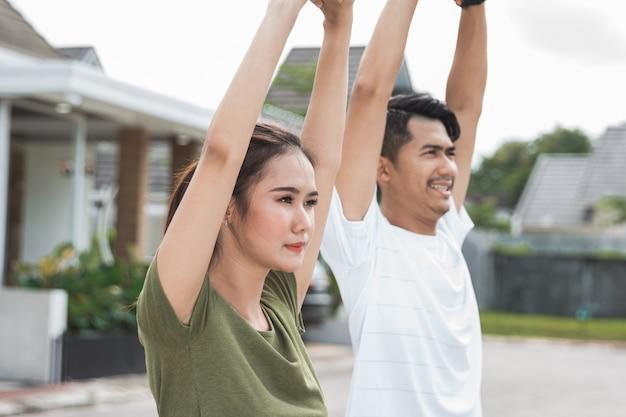 幸せな若いアジア人の運動とウォームアップ