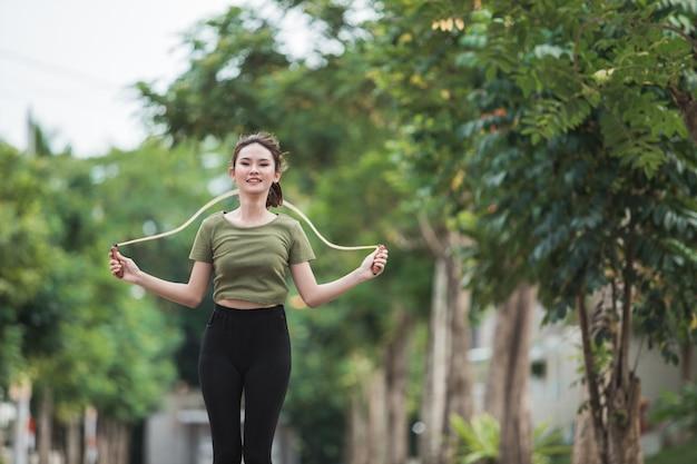 公園で縄跳びを持つ若い女性に合う