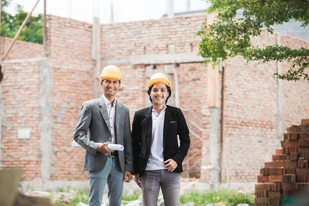 未完成の家の前に立っている建築家およびビルダー