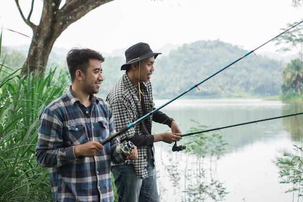 Человек на берегу реки рыбацкой рыбы