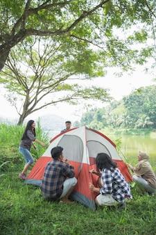 Туристы помогают друг другу готовить палатки