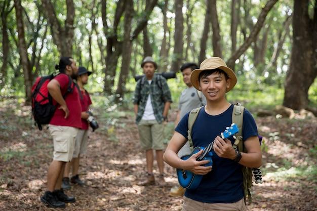 森へハイキングするウクレレを持つ男性
