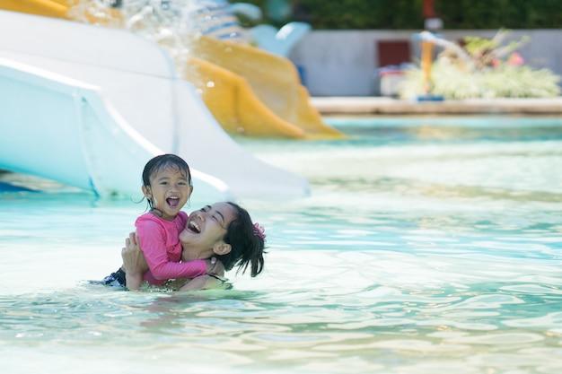 ウォーターパークで泳いでいる母と娘