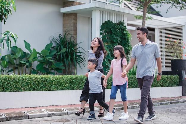 一緒に歩く若い幸せなアジア家族