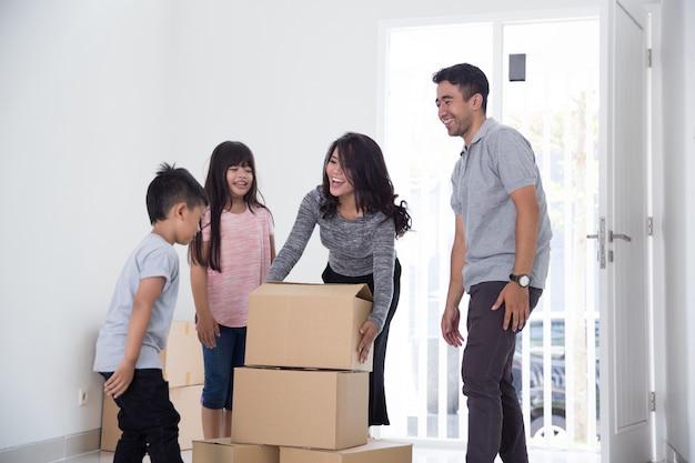 段ボール箱を持つ親と子供。新しい家に引っ越す