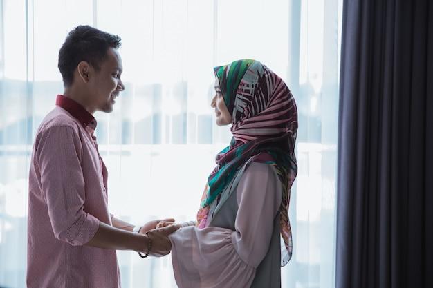 手を繋いでいるロマンチックなイスラム教徒のカップル