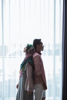Мужчина и женщина стоят спиной к спине