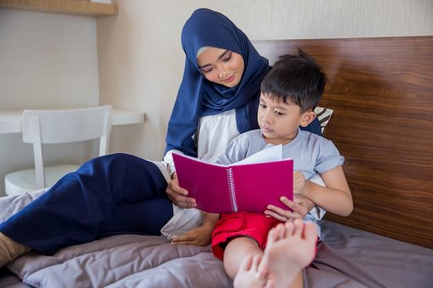 母は彼女の男の子と本を読んで