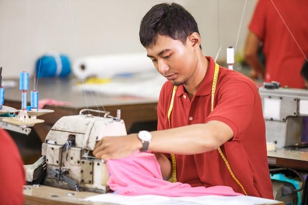 Азиатский рабочий на швейной фабрике с использованием промышленного шитья