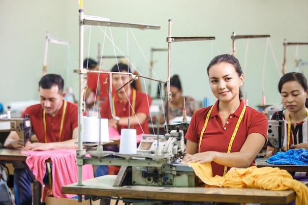 Азиатские рабочие на швейной фабрике шьют с промышленным шитьем м