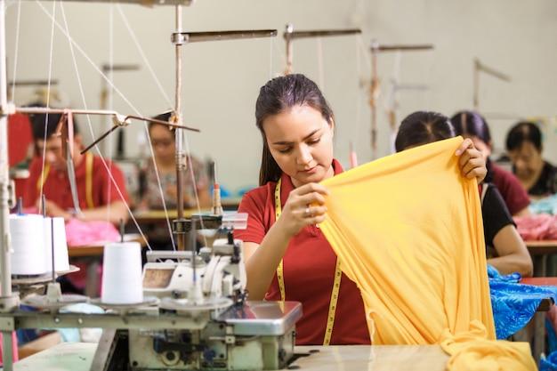Швея на фабрике шитья с использованием промышленного шитья