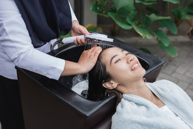 Женщина моет волосы