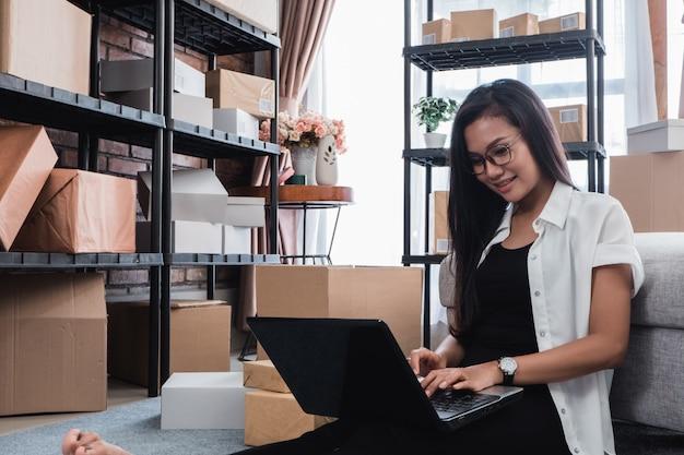 アジアの女性は配送パッケージを確認します