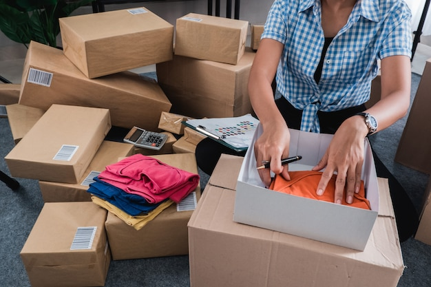 ボックスに置く服の若い女性パッキング
