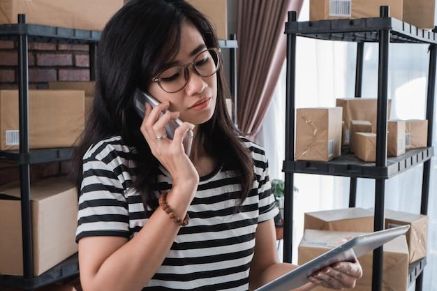 忙しい女性の呼び出しとタブレットを使用して
