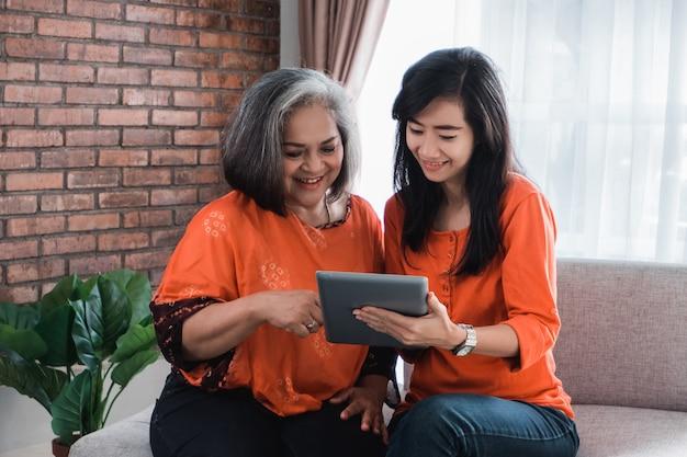 Женщина с помощью планшета с ее зрелой мамой