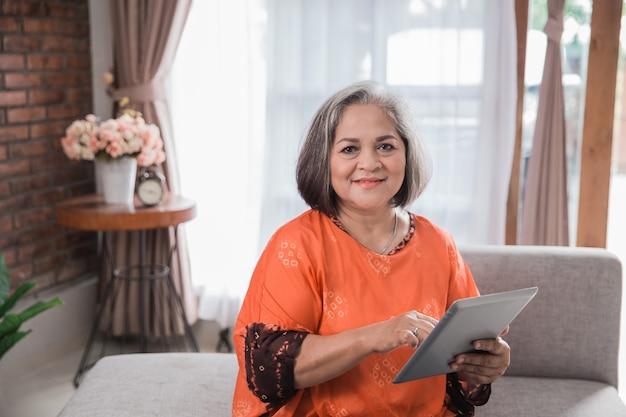 Зрелая женщина с помощью планшетного компьютера