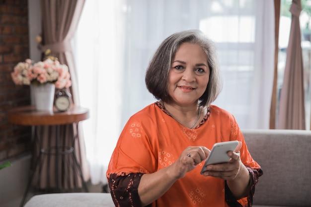 Старшая азиатская женщина используя ее умный телефон