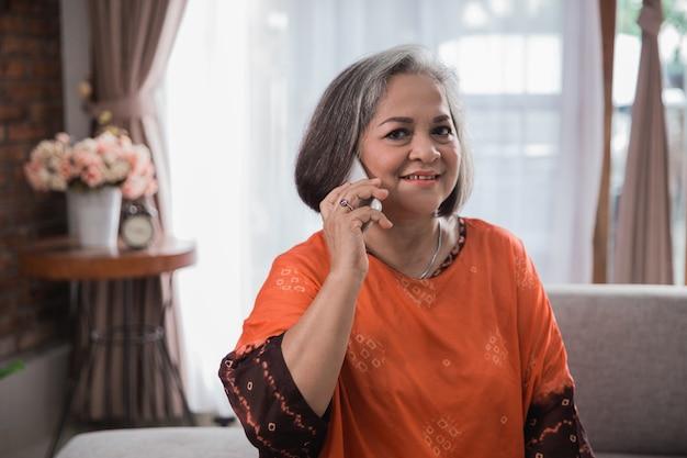 Старшая женщина с помощью телефона