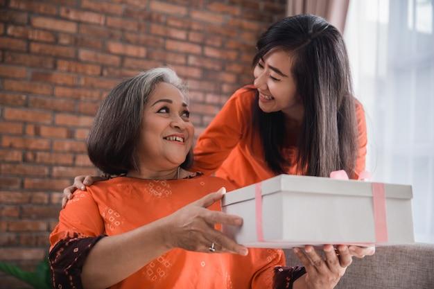 Женщина дарит подарок своей пожилой матери