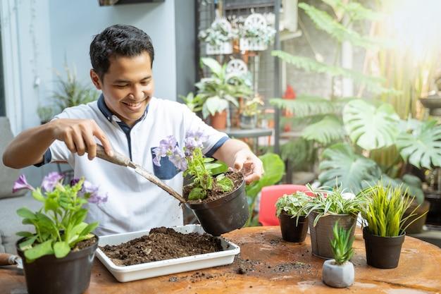 Азиатские мужчины держат горшки и посадочные инструменты, чтобы заменить почву в качестве средства массовой информации