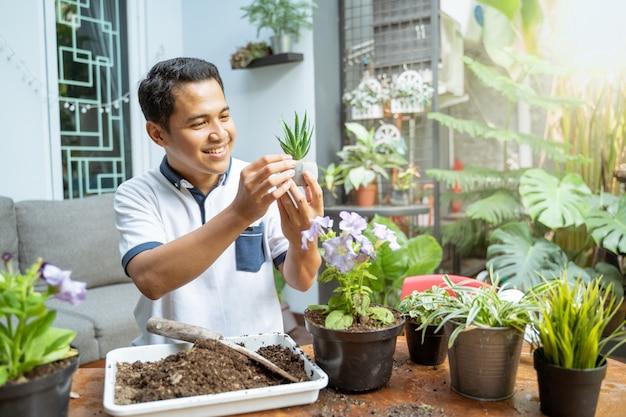 Мужчина с маленьким горшком и растением был поражен его милой формой