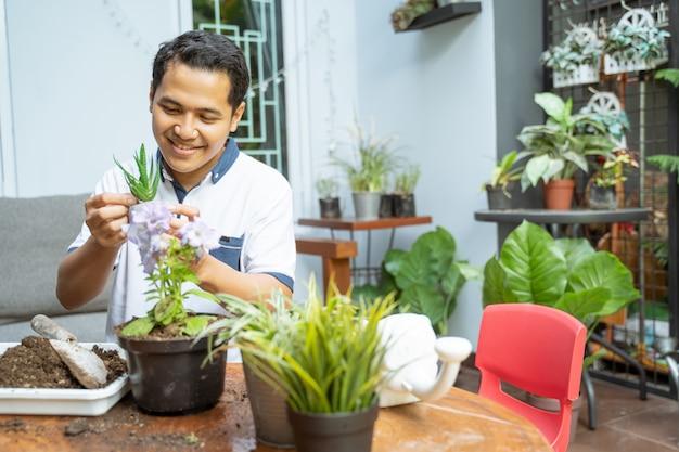 Азиатские мужчины держат маленькие горшки и растения