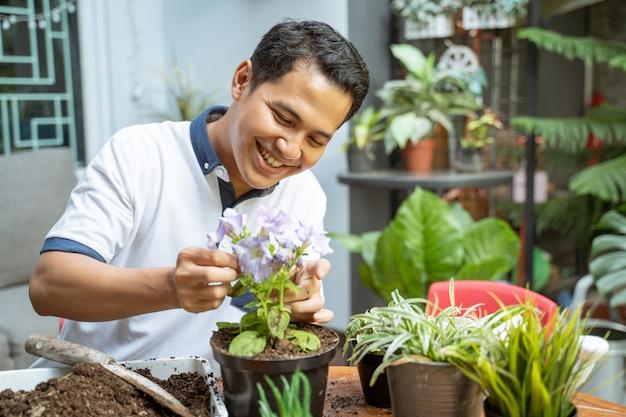 Мужчина счастливо улыбался, держа цветочные горшки в горшках, заботясь